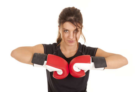 A woman putting her boxing gloves together with a serious expression on her face.