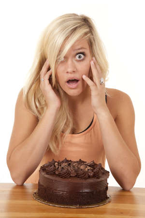 a woman wondering how she is going to eat this chocolate cake all by herself. photo