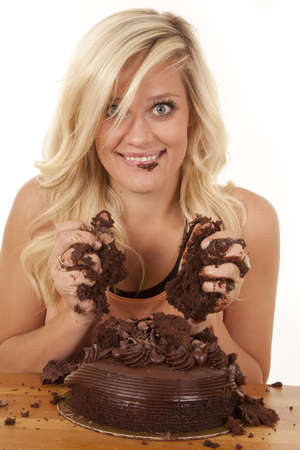A woman with a smile and chocolate on her face with her hands full of chocolate cake.