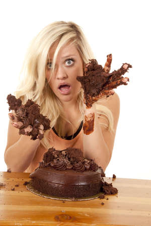 a woman getting caught with her hands in the chocolate cake with a shocked expression on her face. photo