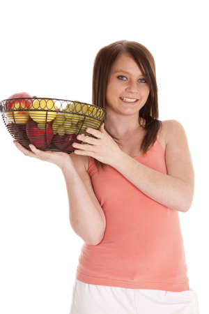A woman with  a smile on her face holding a fruit bowl. photo