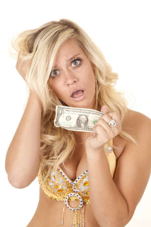 A woman holding on to her last dollar with a shocked and sad expression on her face. photo