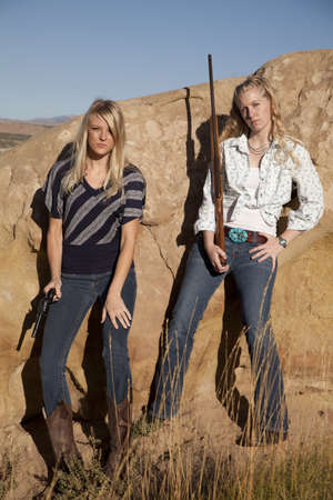 Two women standing together holding their weapons in their western outfits.