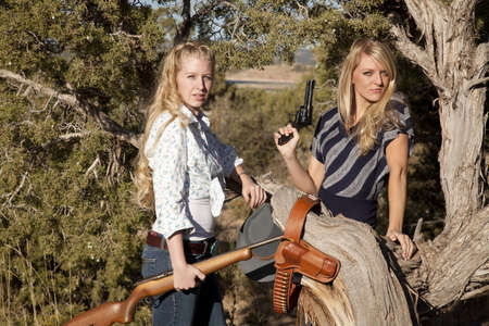 Two women standing together holding their weapons in their western outfits. photo