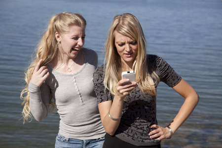 Two friends in the outdoors using a phone, the one is laughing the other is not so happy. photo