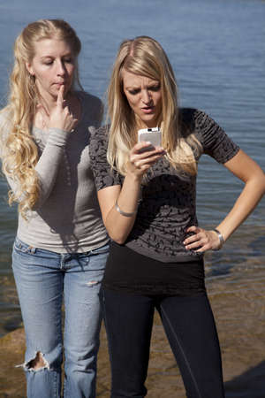 Two friends in the outdoors using a phone, the one is peeking over the others shoulder wanting to see what the text says. photo
