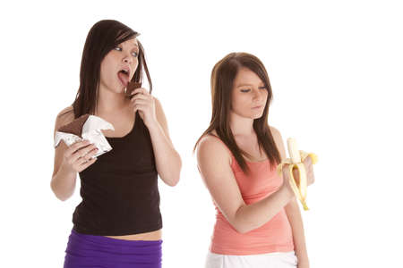 a woman licking and enjoying her chocolate bar while her friend eats a banana. photo