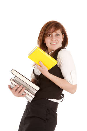 a woman with a stack of books holding on to a yellow book. photo