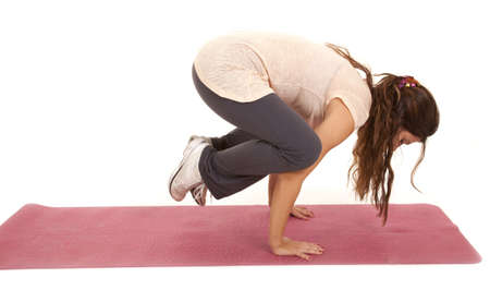 woman doing a yoga pose holding herself off  of the ground. photo
