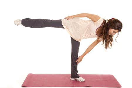 A woman balancing on one leg doing yoga. photo