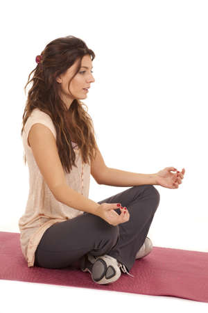 A woman sitting and meditating and relaxing doing a yoga move. Imagens