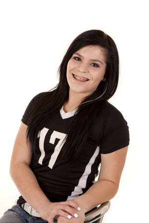 a teenage girl sitting in a chair wearing a jersey with a huge smile on her face. photo