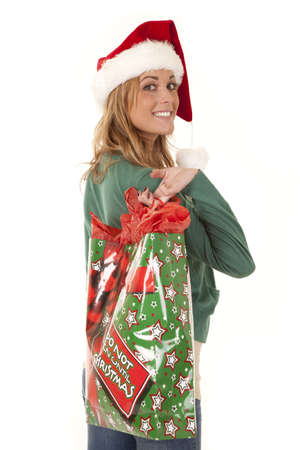 A woman with a Santa hat on holding her Christmas bag over her shoulder with a smile on her face. Imagens