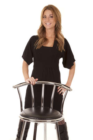 A woman in her black dress standing behind a stool with a smile on her face. Imagens