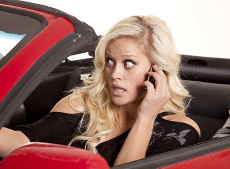 A woman looking out her front windshield with a scared expression on her face talking on her phone. photo