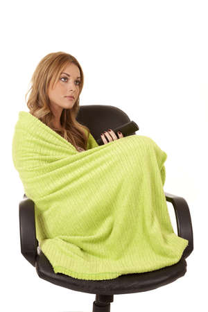 A woman wrapped up in a lime green blanket in a chair with a remote .
