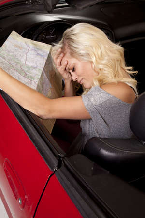 top: A woman sitting in her car with her hand on her head holding on to a road map. Stock Photo