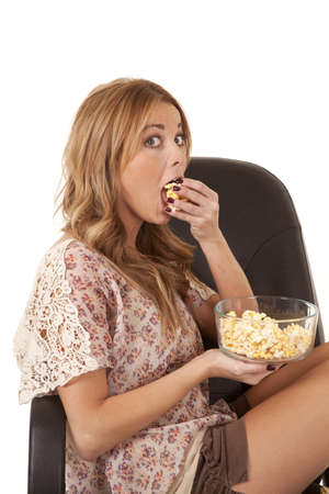 brunett: A woman sitting in her chair holding on to a bowl of popcorn shoving a handful of popcorn in her mouth.
