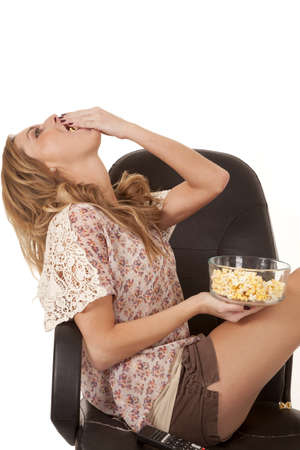 A woman sitting in her chair shoving a big handful of popcorn into her mouth. photo