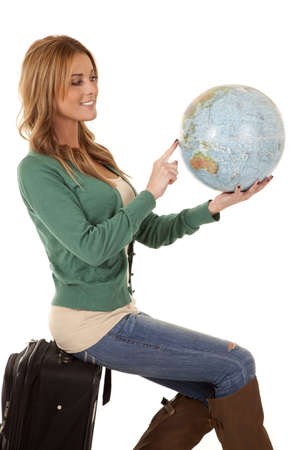 A woman sitting on her suitcase holding on to a world globe pointing out where she wants to go. Stock Photo - 12104397