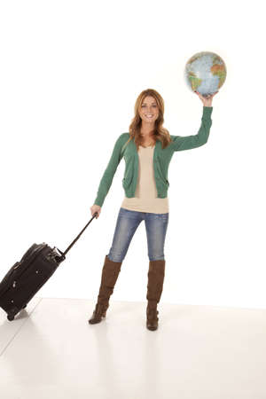 A woman pulling her suitcase and holding a globe in the other hand with a smile on her face. photo