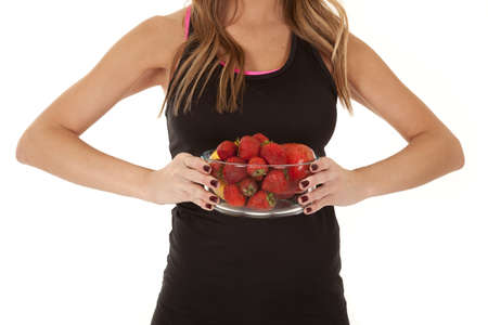 A woman holding  a bowl full of strawberries. photo