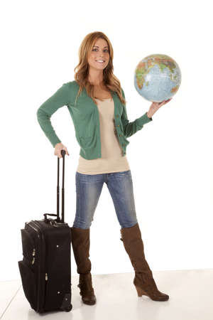 A woman holding on to her suitcase and a globe ready to travel. photo