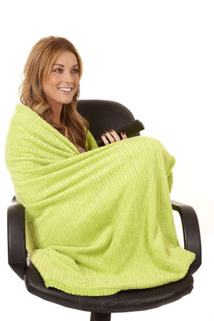 A woman watching tv with the remote in her hands wrapped up in her blanket.