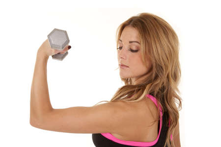 a woman looking down at her arm while she does an arm curl. photo