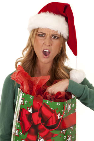 A woman wearing a Santa hat not happy with what is in the bag.