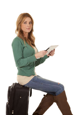 A woman sitting on her suitcase with a serious expression on her face holding on to her tablet. photo