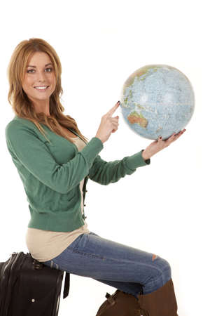 A woman sitting on her suitcase holding on to a world globe pointing out where she wants to go. Stock Photo
