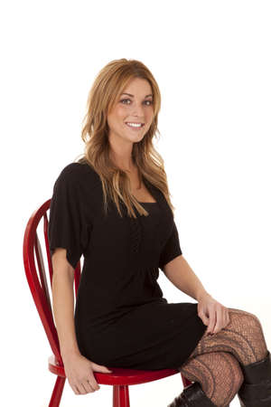 A woman sitting in her chair with a black dress and black boots with  a smile on her face. photo