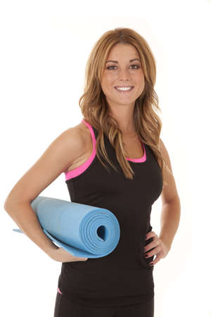 A woman holding on to an exercise mat with  a smile on her face. photo