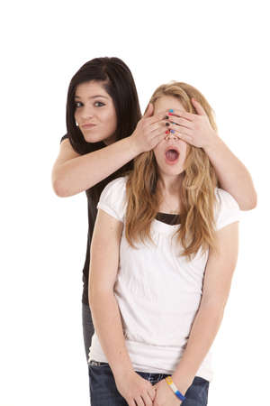 covering eyes: a teenage girl covering up her friends eyes with a smirk on her face.