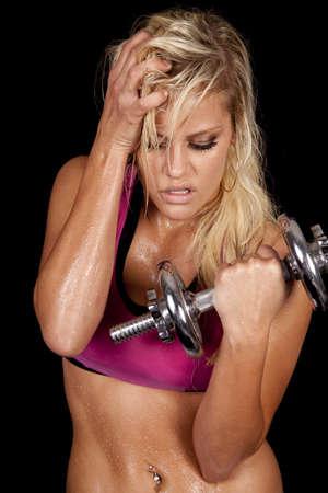 sudoroso: Una mujer est� trabajando con pesas. Ella es caliente y sudoroso.