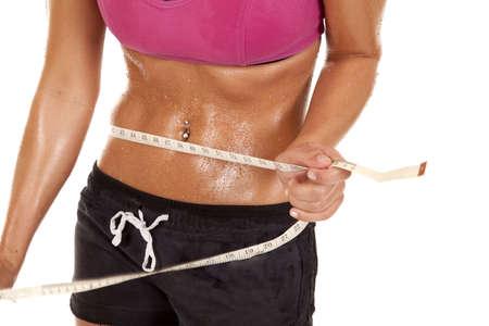 sudando: A cerca de un cuerpo de la mujer con una cinta alrededor de su vientre. Está sudando.