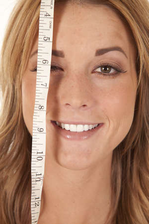 waist up: A woman with a measuring tape over one of her eyes with a smile on her face.