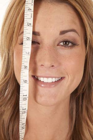 Een vrouw met een meetlint over een van haar ogen met een glimlach op haar gezicht. Stockfoto