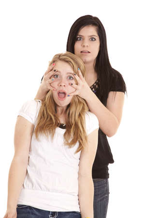 a teenager with her hands on her friends face with a shocked expression on both of their faces. photo