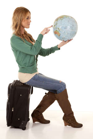 A woman sitting on her suitcase holding on to a world globe pointing out where she wants to go. photo