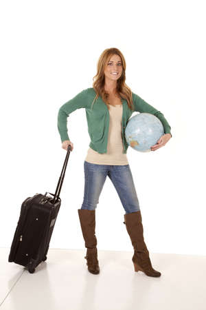 a woman hanging on to her suitcase and a globe with a smile on her face. photo