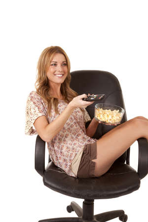 brunett: A woman sitting in her chair with a tv remote and a bowl of popcorn.