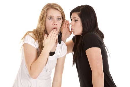 A teenage girl telling her friend a shocking secret in her ear. Banque d'images