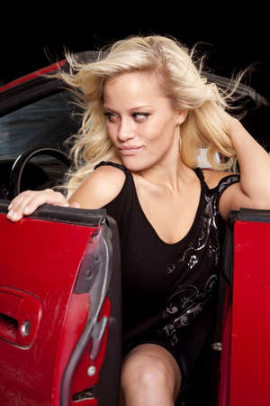 A woman is getting out of her convertible car in a sexy black dress. photo