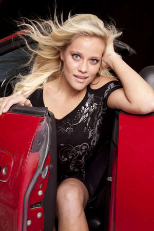 A woman is smiling while stepping out of her red convertible. Stock Photo - 12104343