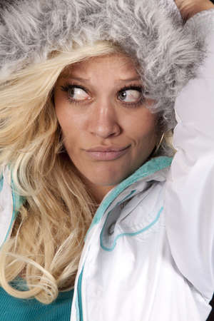 A woman is wearing a white coat with a hood up close. photo
