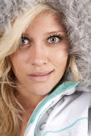 A womans head up close. She is wearing a coat with a hood. photo