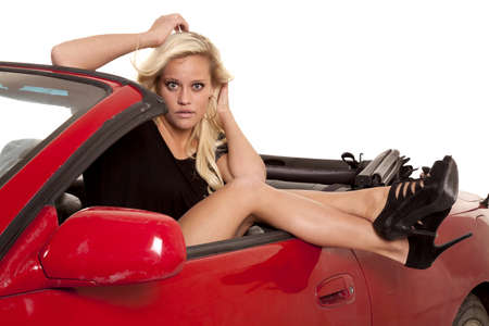 A woman is sitting in her red convertible with her legs over the side. photo
