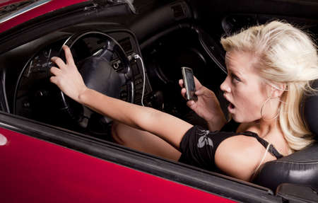 A woman texting on her cell phone while driving with a scared expression on her face. photo